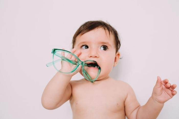 baby putting objects in mouth teething signs symptoms